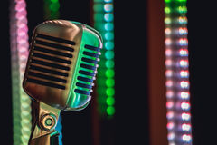 Retro style microphone on stage in the spotlight performance of the musical group. Stock Photos