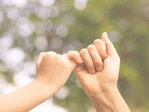 Retro style of mother holding a hand of her kid in spring day outdoors. With green field background royalty free stock photography