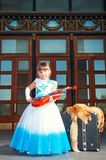 Retro style. Musician, violinist. Girl in a magnificent dress near old suitcases. Violin, fox fur Stock Image