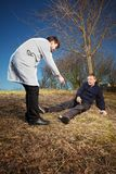 Retro style paramedic helping wounded man in city park. Older man felt while running in park. Wounded calling for help with cellphone Royalty Free Stock Image