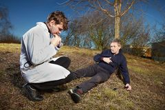 Retro style paramedic helping wounded man in city park. Older men felt while running in park. Wounded calling for help with cellphone Stock Image