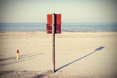 Retro style photo of board sign on a beach. Royalty Free Stock Photo