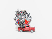 Retro style pickup truck miniature model carrying big aluminum truck engine. Red small vintage retro style pickup truck miniature model carrying big aluminum stock images