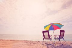 Two deck chairs under sun umbrella on the beach. Retro style picture of seaside with two deck chairs under a multicolored sun umbrella Stock Images