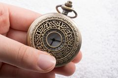 Retro style pocket watch in hand. On white background Royalty Free Stock Photo