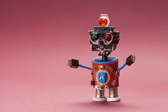 Retro style robot. Toy character with black plastic head, colored green red eyes lamp, blue wire hands. Copy space Royalty Free Stock Images