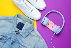 Retro style. 80s. Pop culture. Minimalism. Denim jacket, headphones with audio cassette, white sneakers. Against purple-yellow background. Top view stock image