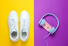 Retro style. 80s. Pop culture. Minimalismalism. Headphones with audio cassette, white sneakers. Against purple-yellow background. Top view stock image