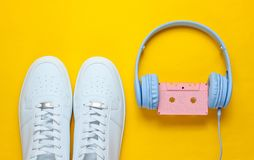 Retro style. 80s. Pop culture. Minimalismalism. Headphones with audio cassette, white sneakers on  yellow background. Top view royalty free stock photos