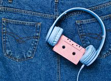 Retro style, 80s. Headphones, audio cassette on back pocket of jeans. Pop culture. Minimalism. Top view stock photo