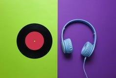 Retro style. 80s. Vinyl record, headphones on a green-purple background. Top view. Minimalism royalty free stock photo