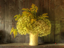 Retro style still life of dried flowers in vase. Still life image of dried flowers in rustic vase against weathered wooden background Royalty Free Stock Photo