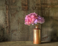 Retro style still life of dried flowers in vase. Still life image of dried flowers in rustic vase against weathered wooden background Royalty Free Stock Images