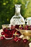 Cherry liqueur in crystal carafe and fresh fruits Royalty Free Stock Photos