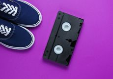 Retro style stuff 80s. Videotape, jeans, sneakers on purple background. Top view royalty free stock photos