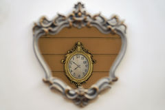 Retro Style Wall Clock Reflection Inside a Mirror on A Wall. Retro style wall clock reflection inside a mirror on a white wall royalty free stock image