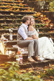 Retro style wedding couple sitting on stone steps and hugging in autumn forest, surrounded by beautiful decoration. Stock Image