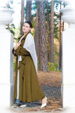 Retro style woman. Retro style beautiful sensual young woman wearing vintage long coat standing in forest. Poetic romantic mood Stock Images