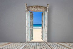 Retro style wooden door in grey color room opened to the beach Stock Images