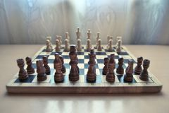 Retro style wooden material chessboard with chess pieces set ready for strategic mind game. Focus on pawns. stock photo