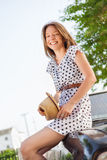 Retro style young woman sitting on the car Stock Photos