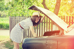 Retro style young woman standing next to the car Royalty Free Stock Photography