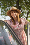 Retro style young woman standing next to car Royalty Free Stock Images