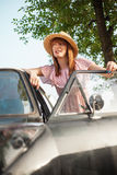 Retro style young woman standing next to car Royalty Free Stock Photo