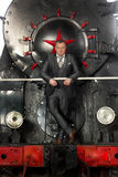 Retro styled businessman in suit posing on steam locomotive stock photo