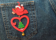 Retro styled Christmas decoration hanging on back pocket of jeans. Stock Images
