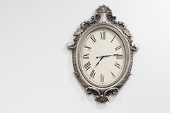 Retro styled clock on white wall Stock Photography