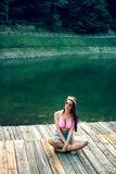 Retro styled girl posing on mountain lake. Royalty Free Stock Images