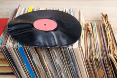 Retro styled image of a collection of old vinyl record lp`s with sleeves on a wooden background. Browsing through vinyl records co Stock Images