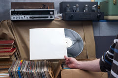 Retro styled image of a collection of old vinyl record lp`s with sleeves on a wooden background. Browsing through vinyl records co Royalty Free Stock Photography