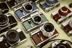 Retro styled image of colorful photo cameras on a flee market Stock Photography