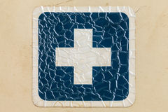 Retro styled image of a cracked blue cross label Stock Photos