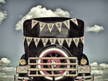 Retro styled image of an old car with just married decoration Stock Image