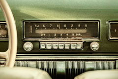 Retro styled image of an old car radio. Inside a green classic car Royalty Free Stock Images