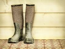Retro styled image of an old pair of boots. Against a wooden background stock images