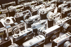 Retro styled image of old photo cameras on a flee market Stock Photos