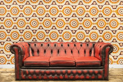 Retro styled image of an old sofa against a vintage wallpaper wa Stock Photo