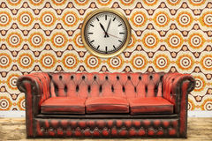 Retro styled image of an old sofa and clock against a vintage wa Stock Photos
