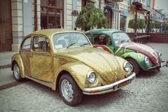 Retro styled image of a row of vintage Volkswagen Beetles Stock Images