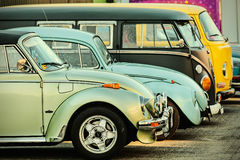 Retro styled image of a row of vintage Volkswagen Beetles and Tr Stock Images