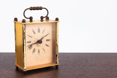 Retro styled image of vintage square table clock on a wooden table. stock photography