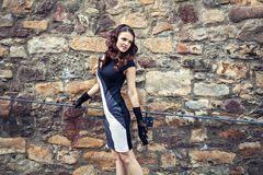 Retro-styled lady in black dress at old stone wall Stock Image