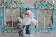 Funny small Santa - Christmas card. Retro styled New Year card with plasticine Father Frost and old house Royalty Free Stock Photography