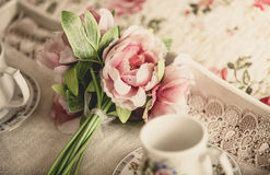 Retro styled photo of pink flowers lying on tray with teacups Royalty Free Stock Photos