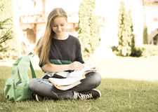 Retro styled portrait of school or college girl sitting on the grass with book and bag studying in a park. Stock Photography