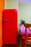 Retro-styled red refrigerator in the kitchen room Stock Photos